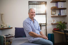 Portrait of smiling senior male patient sitting on bed Stock Photos