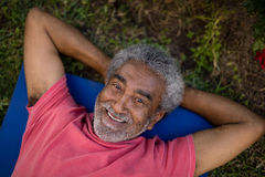 Portrait of smiling senior male resting while lying on exercise mat royalty free stock images
