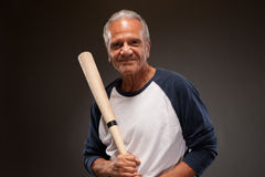 Portrait of a smiling senior man with a baseball bat Stock Photos