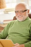Portrait of smiling senior man with book Stock Images