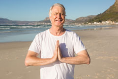 Portrait of smiling senior man doing yoga at beach Royalty Free Stock Photo