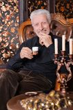 Portrait of smiling senior man drinking coffee at home stock photo