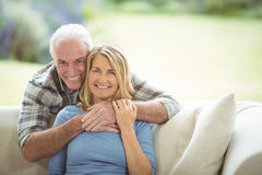 Portrait of smiling senior man embracing a woman in living room Stock Photography