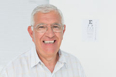 Portrait of a smiling senior man with eye chart in background Royalty Free Stock Image