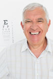 Portrait of smiling senior man with eye chart in background Stock Images