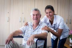 Portrait of smiling senior man and female doctor in living room Stock Image