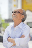 Portrait of smiling senior man with glasses, arms crossed, outdoors in Beijing Stock Photos