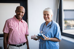 Portrait of smiling senior man and healthcare worker. Portrait of smiling senior men and healthcare worker with blood pressure gauge at nursing home stock photography