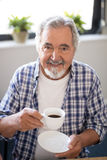 Portrait of smiling senior man holding coffee cup. While sitting at nursing home Stock Image