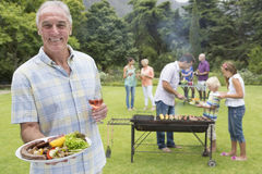 Portrait of smiling senior man holding plate of barbecue and wine with family in background Royalty Free Stock Photo