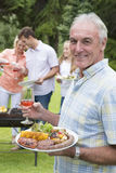 Portrait of smiling senior man holding plate of barbecue and wine Royalty Free Stock Photo