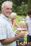 Portrait of smiling senior man holding plate of barbecue and wine stock photography