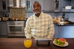 Portrait of smiling senior man in kitchen royalty free stock photography