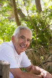 Portrait of smiling senior man leaning on wooden fence Stock Image