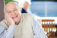 Portrait Of Smiling Senior Man At Nursing Home. Portrait of smiling senior man sitting at nursing home with grandson in background Stock Photos