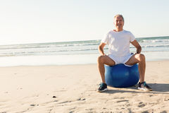 Portrait of smiling senior man sitting on ball against sea Royalty Free Stock Photos