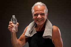 Portrait of a smiling senior man with a towel and water bottle. Senior man with a towel and water bottle Stock Photo