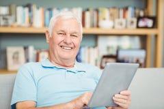 Portrait of smiling senior man using digital tablet Royalty Free Stock Photo