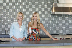 Portrait of smiling senior mother and daughter standing in kitchen Royalty Free Stock Image