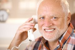 Portrait of smiling senior using landline phone. Closeup portrait of smiling senior man using landline phone, looking at camera Stock Images
