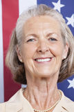 Portrait of smiling senior woman against American flag Royalty Free Stock Photography