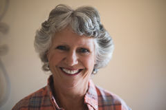Portrait of smiling senior woman against wall at home Stock Images
