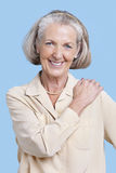 Portrait of smiling senior woman in casuals with hand on shoulder against blue background Royalty Free Stock Photography
