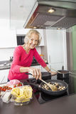Portrait of smiling senior woman cooking food in kitchen Stock Photos