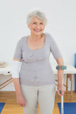 Portrait of a smiling senior woman with crutch Royalty Free Stock Photo
