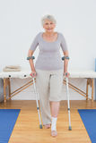 Portrait of a smiling senior woman with crutches in hospital gym Stock Photography