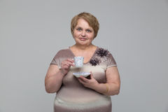 Portrait of smiling senior woman with cup of tea Stock Photo