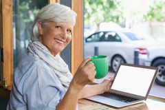 Portrait of smiling senior woman holding coffee cup while sitting at table. In cafe shop Royalty Free Stock Image