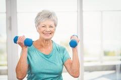Portrait of smiling senior woman holding dumbbell Stock Photos