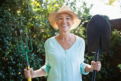 Portrait of smiling senior woman holding garden fork and shovel Stock Images
