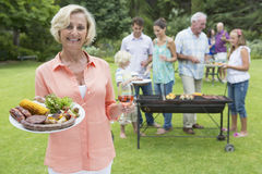 Portrait of smiling senior woman holding plate of barbecue and wine with family in background Royalty Free Stock Image