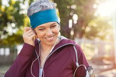 Mature woman adjusting earphones before running. Portrait of smiling senior woman listening to music after running. Healthy mature woman wearing blue headband royalty free stock photography