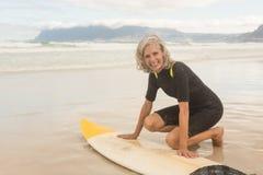 Portrait of smiling senior woman preparing for surfboarding stock images