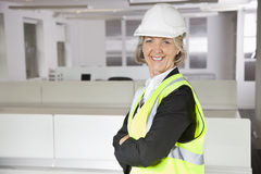 Portrait of smiling senior woman in reflector vest and hard hat at office. Portrait of smiling senior women in reflector vest and hard hat at office Royalty Free Stock Images