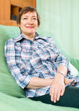 Portrait of smiling senior woman relaxing in couch Stock Photos