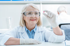 Portrait of smiling senior woman scientist analyzing pill in hand Royalty Free Stock Photo