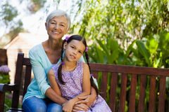 Portrait of smiling senior woman sitting with arm around girl on wooden bench Stock Photo