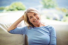 Portrait of smiling senior woman sitting on sofa in living room. At home Royalty Free Stock Photos