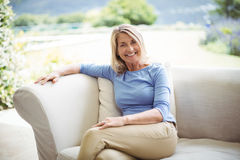 Portrait of smiling senior woman sitting on sofa in living room. At home Stock Photos