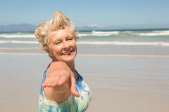 Portrait of smiling senior  woman standing against clear sky. At beach Royalty Free Stock Photo