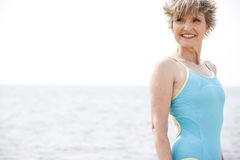 Portrait of a smiling senior woman in a swimsuit at the beach Royalty Free Stock Image