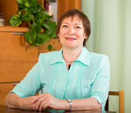 Portrait of smiling senior woman at table Stock Photography