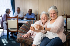 Portrait of smiling senior woman taking selfie with friend. Portrait of smiling senior women taking selfie with friend through mobile phone at nursing home Stock Image