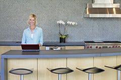 Portrait of smiling senior woman using laptop in kitchen Royalty Free Stock Photos