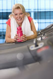 Portrait of smiling senior woman with water bottle leaning on treadmill at health club Royalty Free Stock Photos
