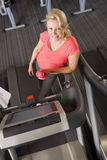 Portrait of smiling senior woman with water bottle leaning on treadmill in health club Royalty Free Stock Images